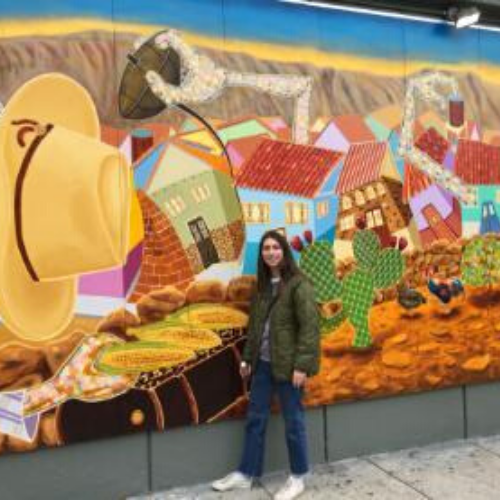 Photo of Austin Nelson in front of a colorful mural