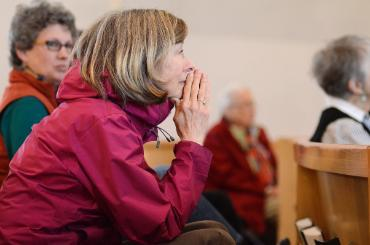 woman alum praying in chapel