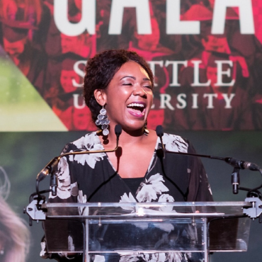 A photo of Essence Russ standing in front of a podium at an SU Gala