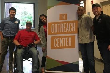 Students standing next to Outreach Center sign