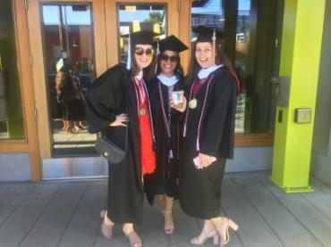 A photo of three women wearing graduation robes