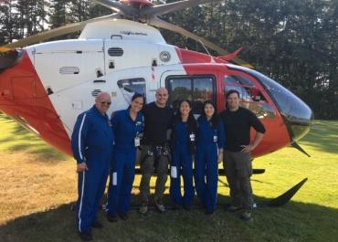 6 people standing in front of a red and white helicopter sitting on a field.