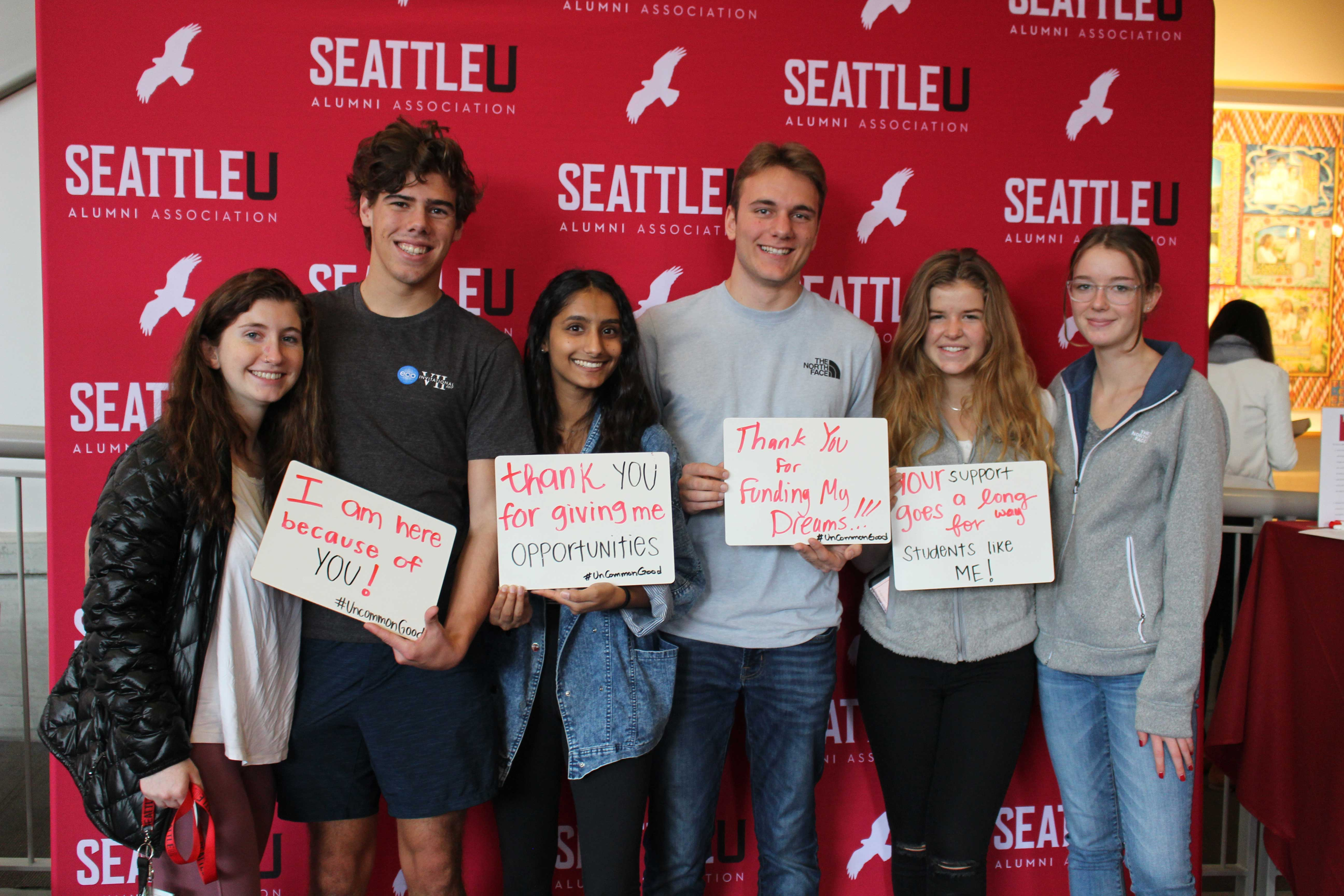 Thankful students holding signs at a photobooth