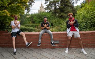 A photo of three male basketball athletes on campus wearing masks and forming their hands into the Redhakw symbol