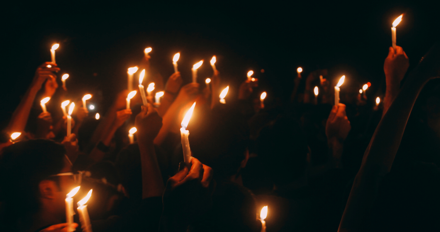A crowd of people holding candles in vigil.