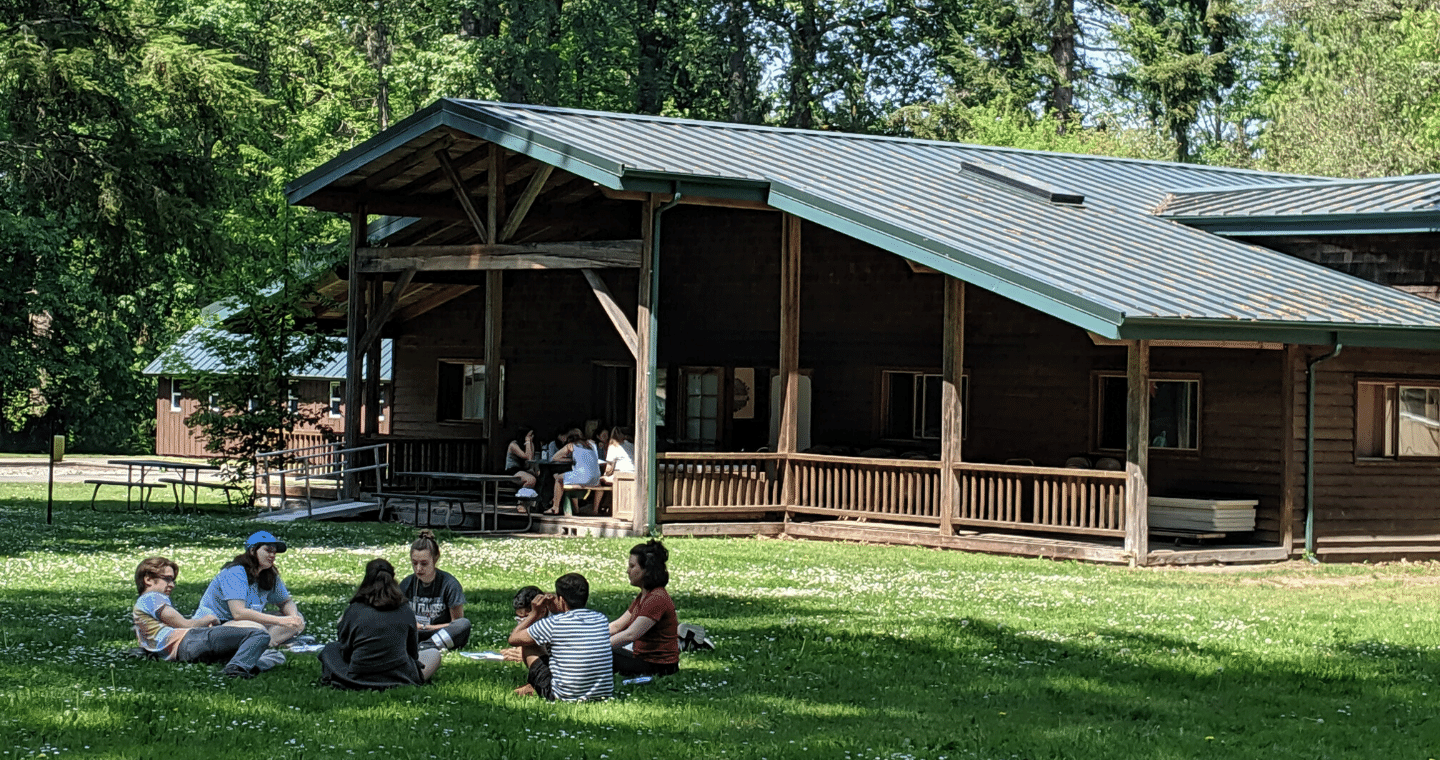 A group of students sits in a circle in the grass in front of a wooden cabin.