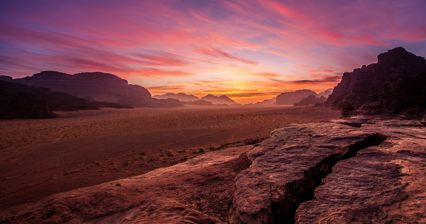 A sunset in the desert, with sand dues on the horizon