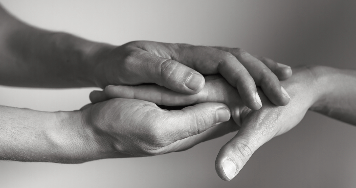 A pair of hands enclosed around another person's hand.