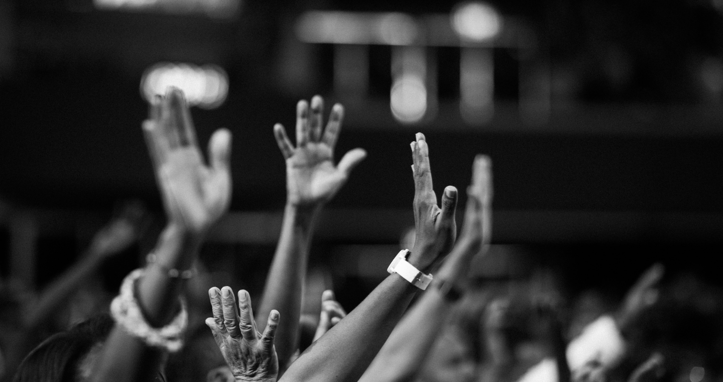 black and white photo of group praying with raised hands in prayer
