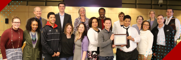 A group of Seattle University and Seattle Public Schools staff as well as students from Washington Middle School pose with an award from SPS to Seattle U for SUYI
