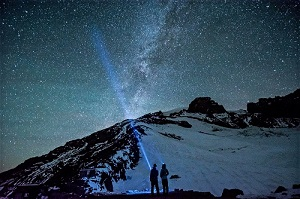 Two people on a mountain under a starry night sky
