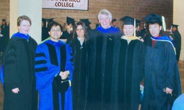 Paul Milan (center) and colleagues at SU commencement