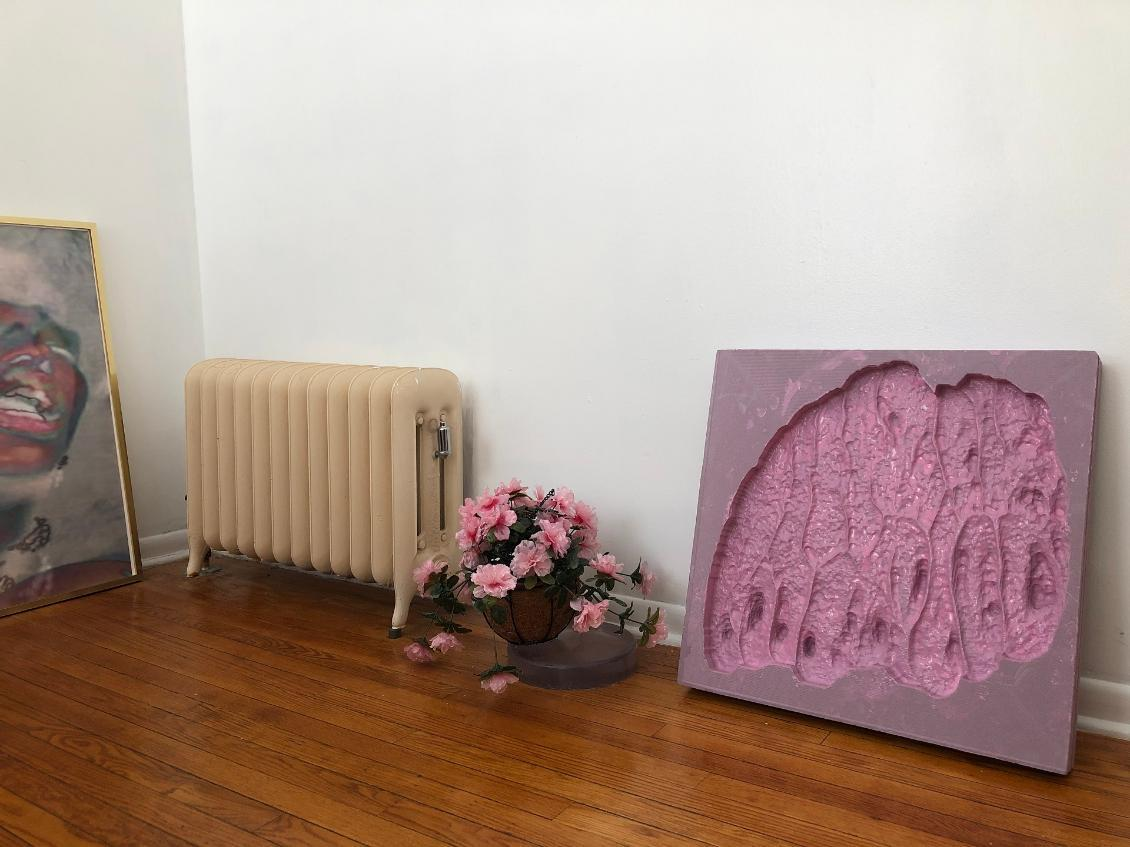 Image of artwork with two paintings, a radiator and flowers