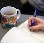 Student writing in journal with cup of coffee