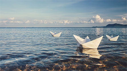 three paper boats on a lake