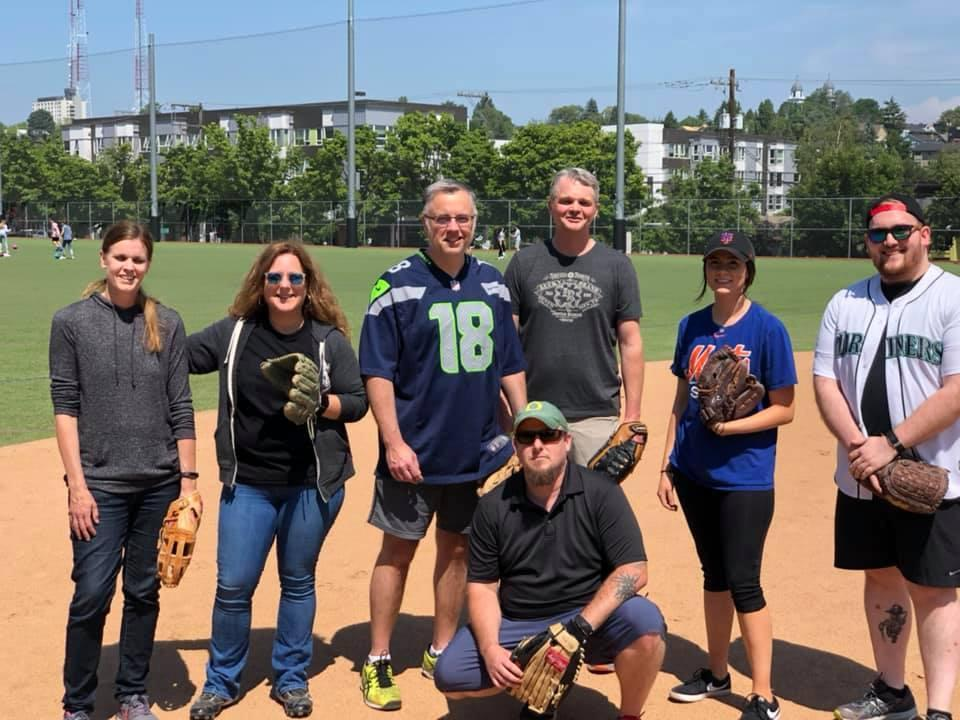 A group of people with baseball mitts at a baseball field on a sunny day