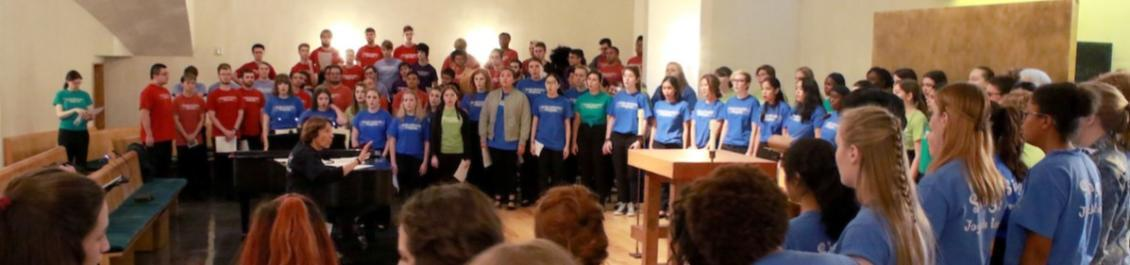 SU Choir in multicolored shirts performing in the Chapel of St. Ignatius