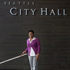 Karinda Harris, woman standing in front of City Hall sign.