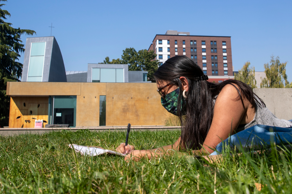 Student in a mask studying in the grass