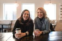 photo of Coya Paz Brownrigg and Chloe Johnston sitting at a wooden table and holding coffee mugs, smiling at the camera.