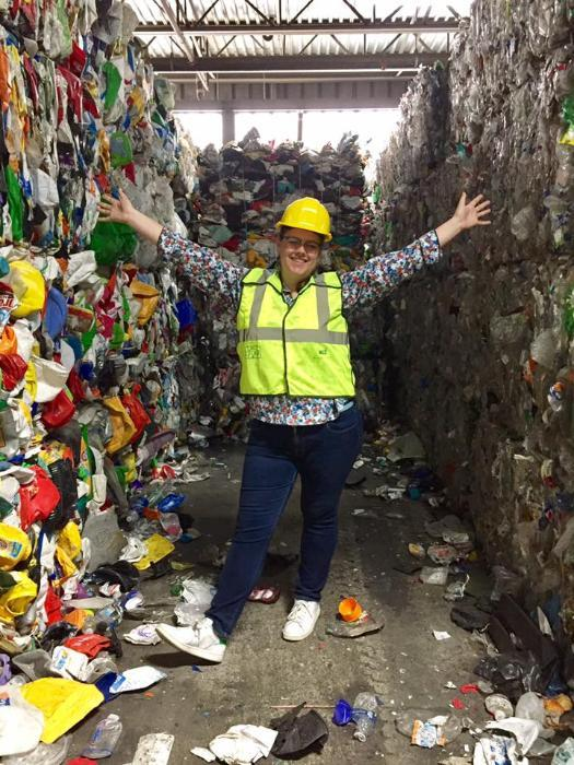 Jessie Dirks at the Cascade Recycling Center surrounded by recycling.