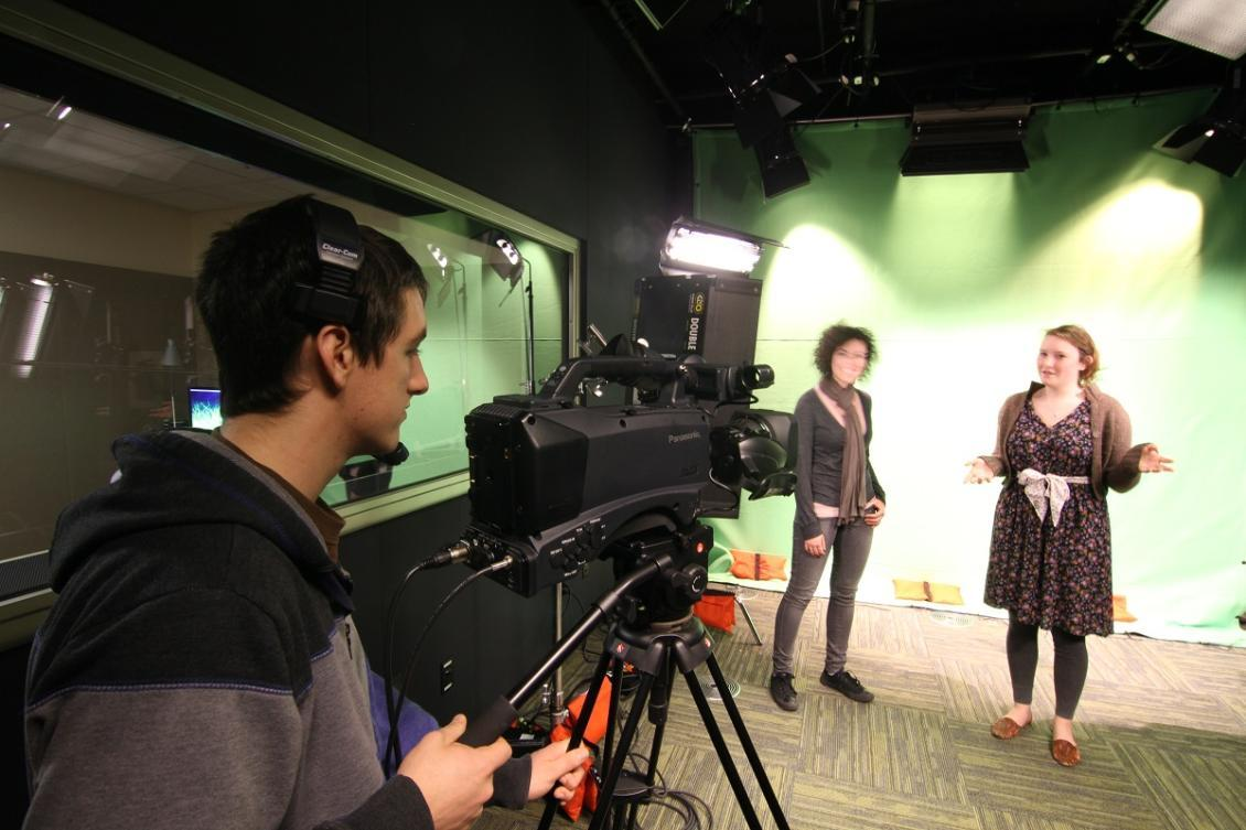 Male student filming two female students in the studio