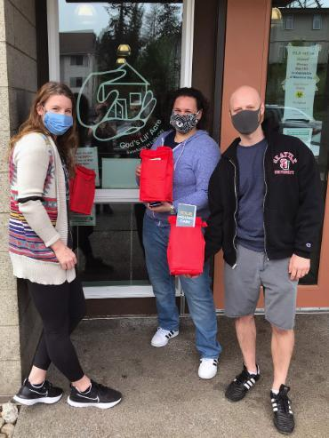Sarah Dean, Jen Tate and Brad Fifield standing in front of GLA holding red wound care kits for the homeless
