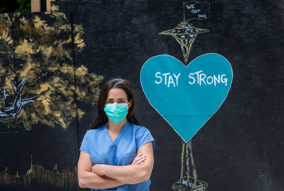 Sarah Welch is wearing a surgical mask and scrubs and is standing with her arms crossed in front of a mural of the space needle with a heart with words stay strong on it