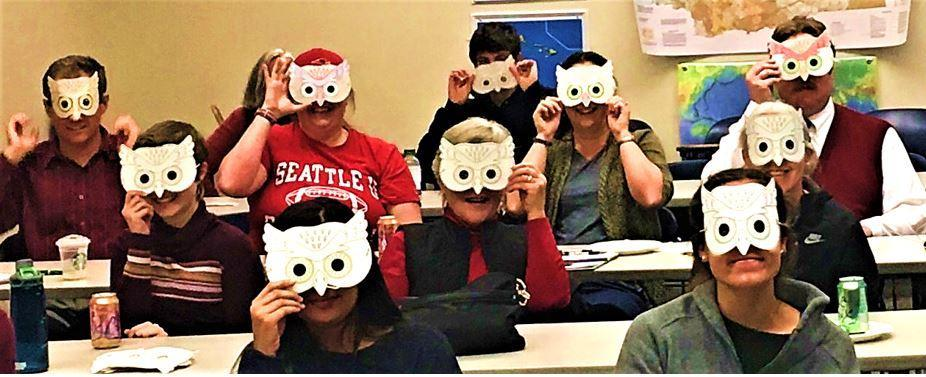 SMART Friday attendees wear owl masks at a talk about owls and computational neuroscience