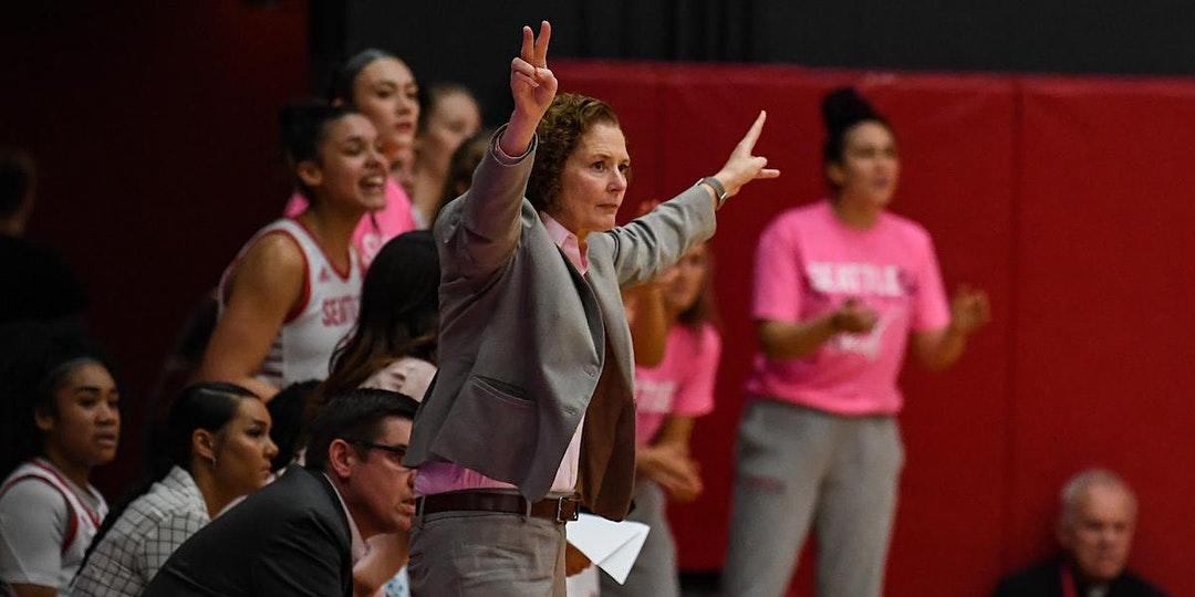 Women's Basketball head coach cheers on the players during a game