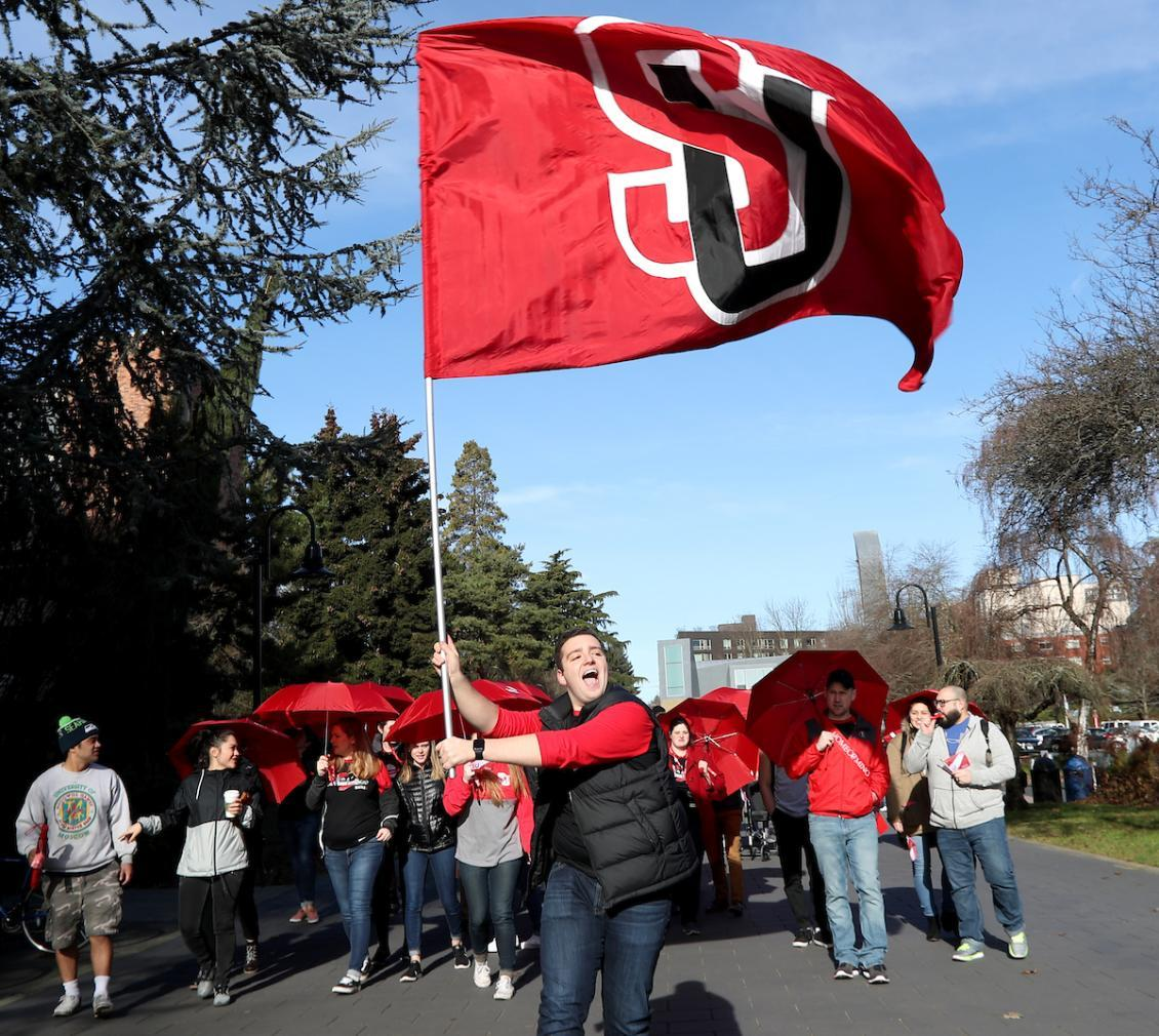 student holding an Seattle University flag at a parade