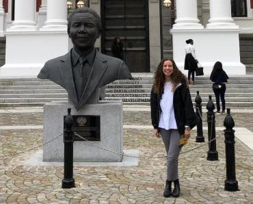 Student Sienna Miller standing next to a statue of Nelson Mandela in Cape Town, South Africa
