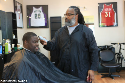 Earl Lancaster giving a trim to Cameron Dollar, Seattle University's head coach of men's basketball