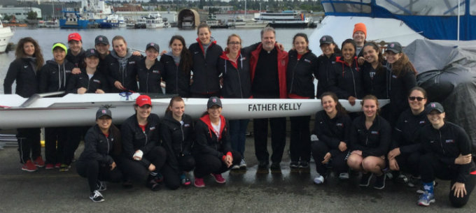 Group photo of the Women's Crew Team and Father Kelly