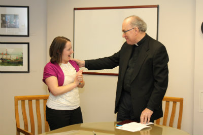 Laura Hauck-Vixie reacts as Fr. Steve informs her she will receive the 2015 Excellence in Staff Leadership Award