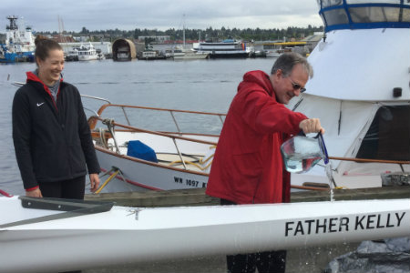 Father Kelly christening a rowing shell