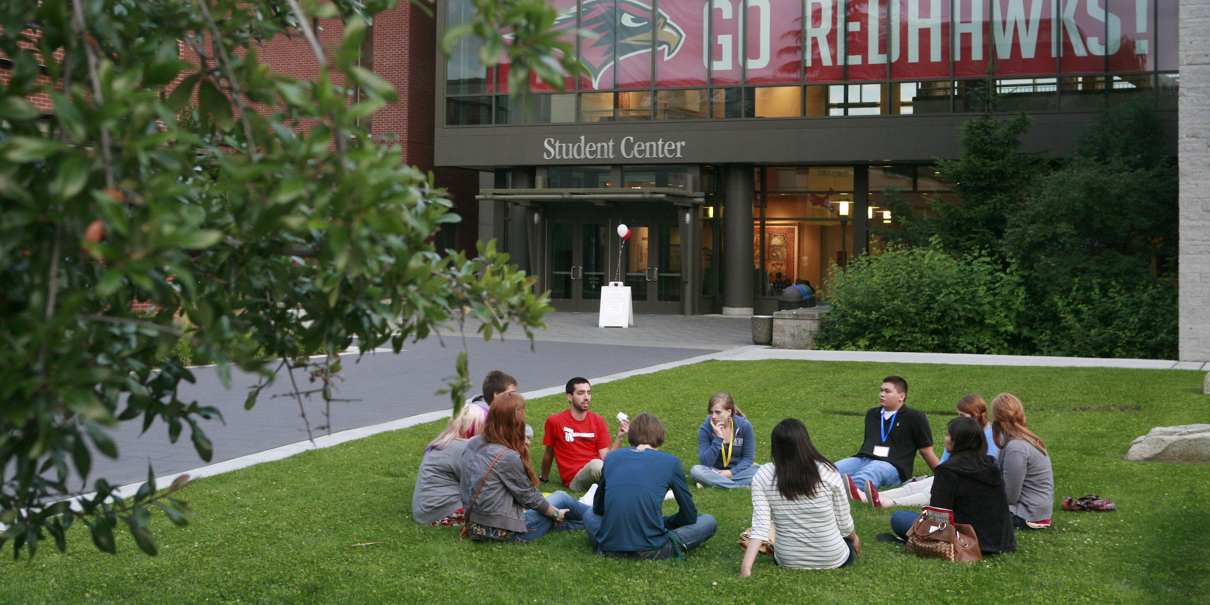 a group of students sitting in a circle on the lawn in front of the Student Center