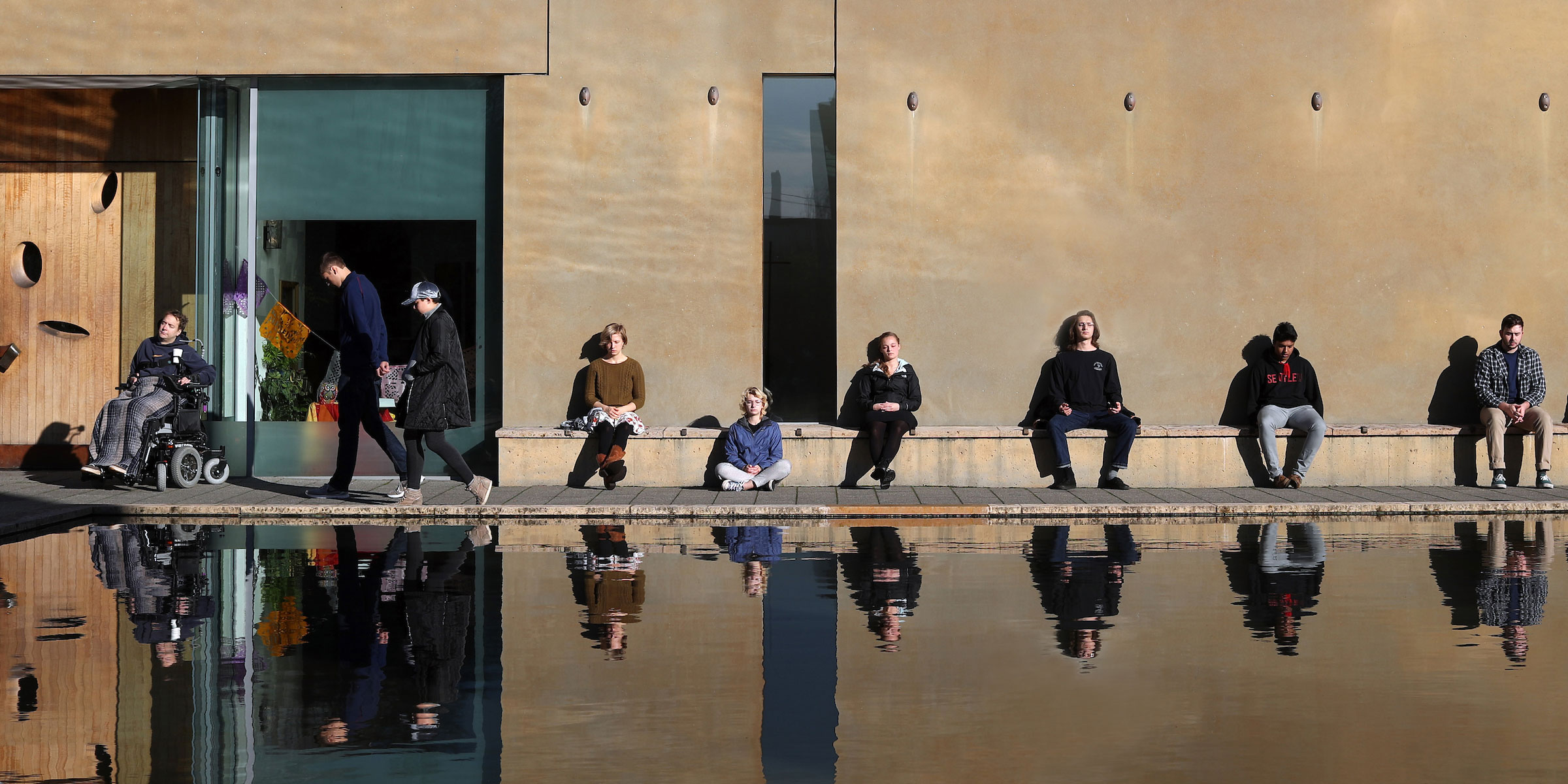 students soak in the sun on the benches of St. Ignatius chapel and the Reflecting Pool