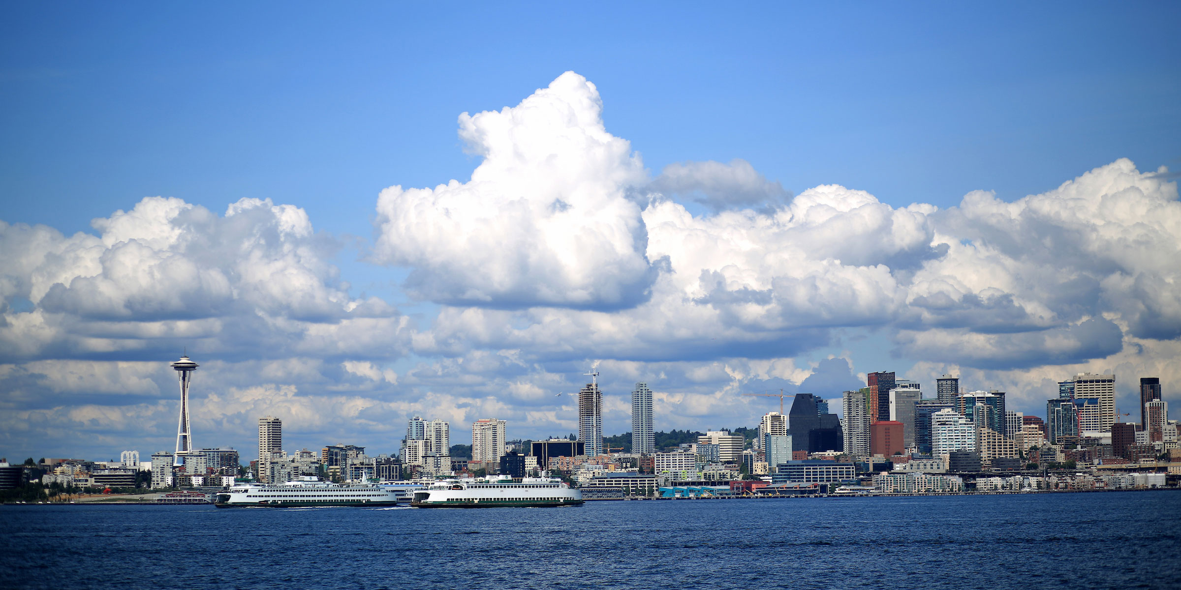 view of blue skies and puffy white clouds above the Seattle skyline and waterfront from Alki Beach in West Seattle