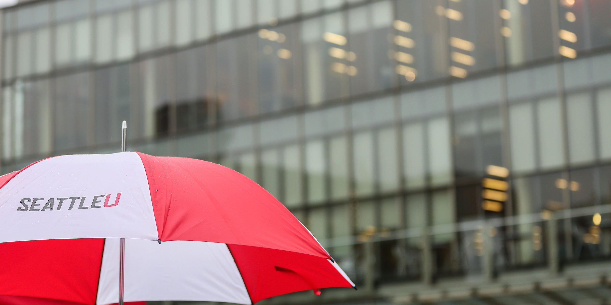 bright red and white SU umbrella on a rainy day