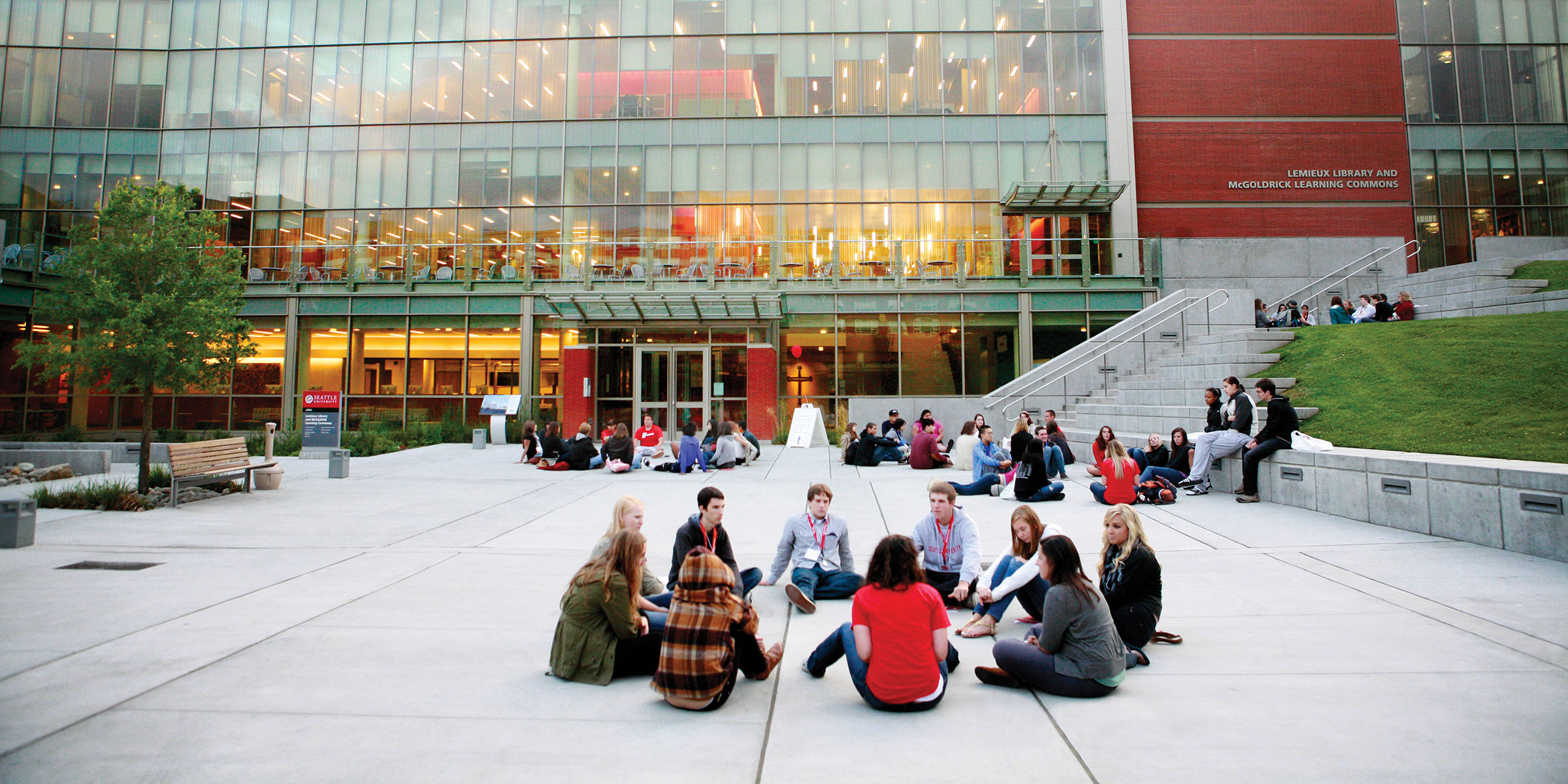 a group of students talk and sit in a circle in the Lemieux Library plaza