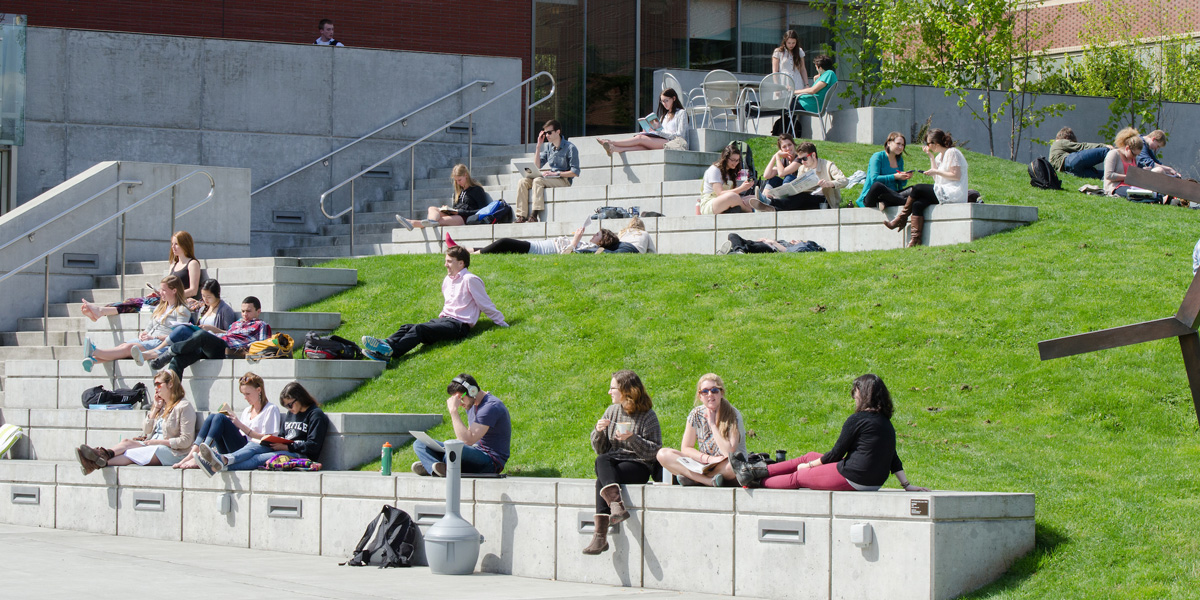 students studying outside Lemieux Library on a sunny Spring day