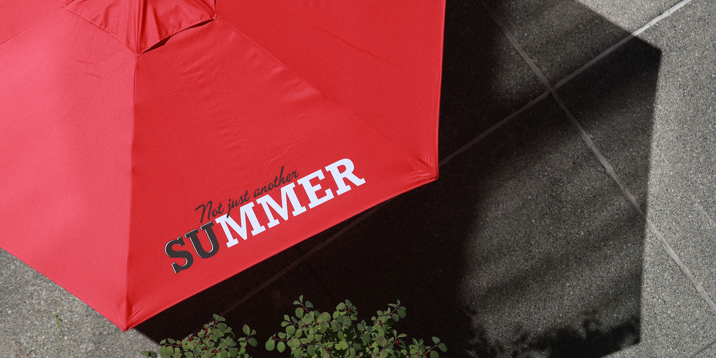 birds eye view of a bright red patio umbrella that reads SU Summer