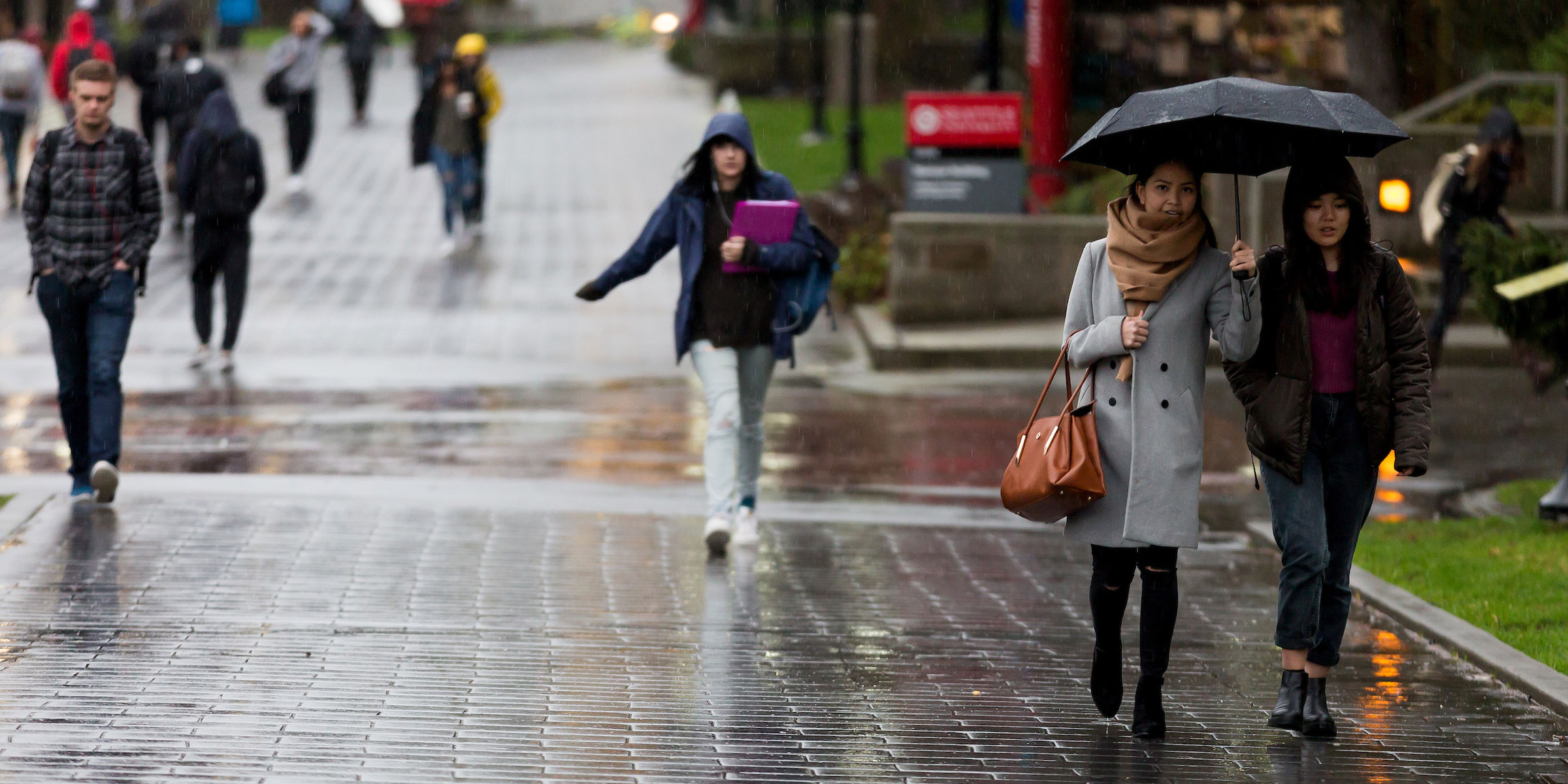 students walk through campus on a rainy day