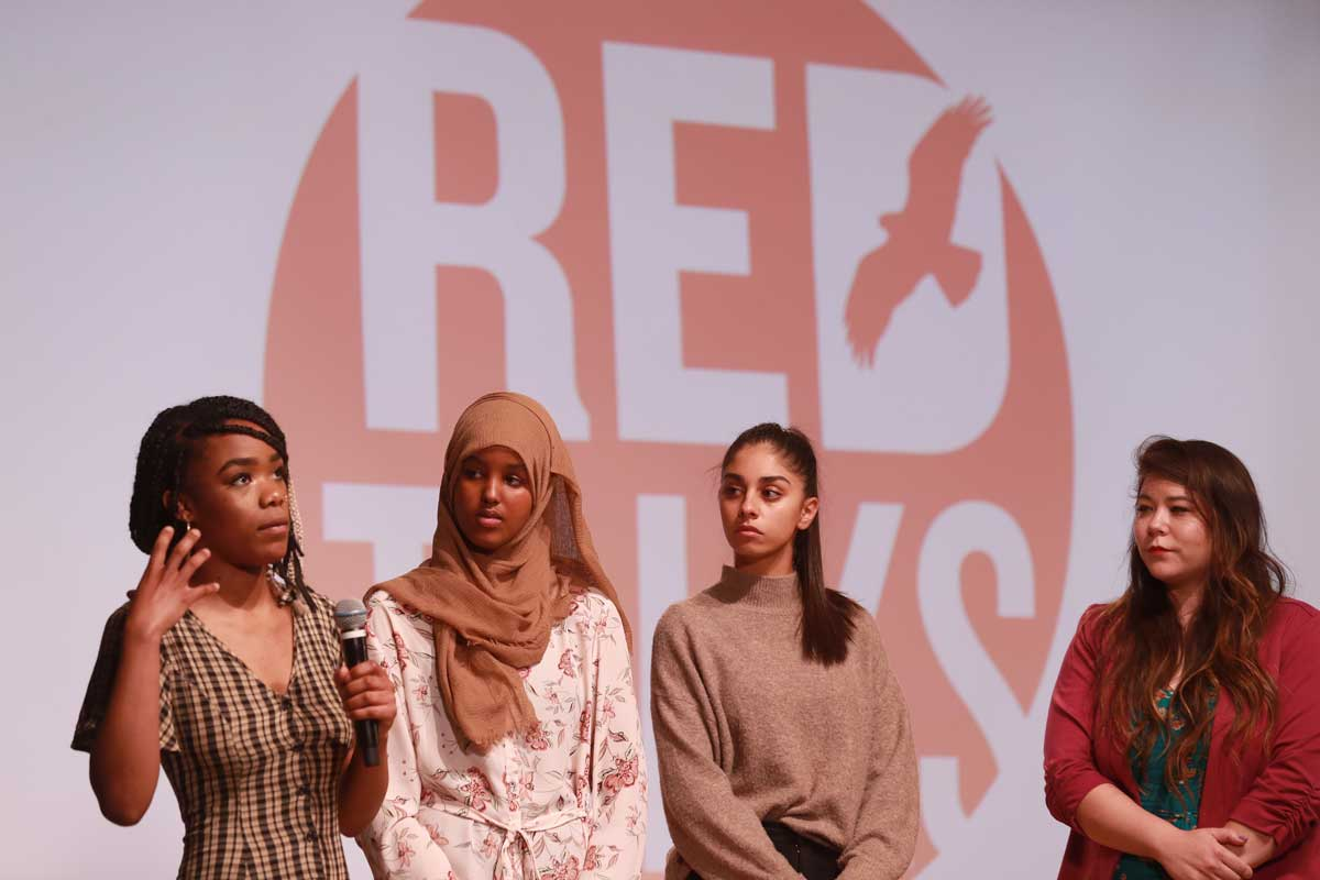 Four student speakers, all women of color, on stage during the Red Talks Student Edition event