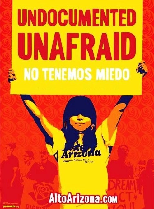 woman holding up a sign that says undocumented unafraid and again in spanish