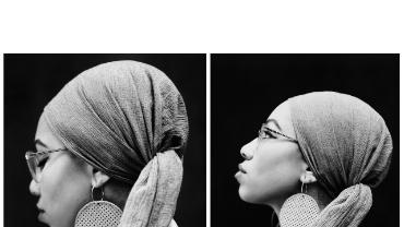 black & white profile head shot of Sudanese woman in headscarf and glasses and big earrings