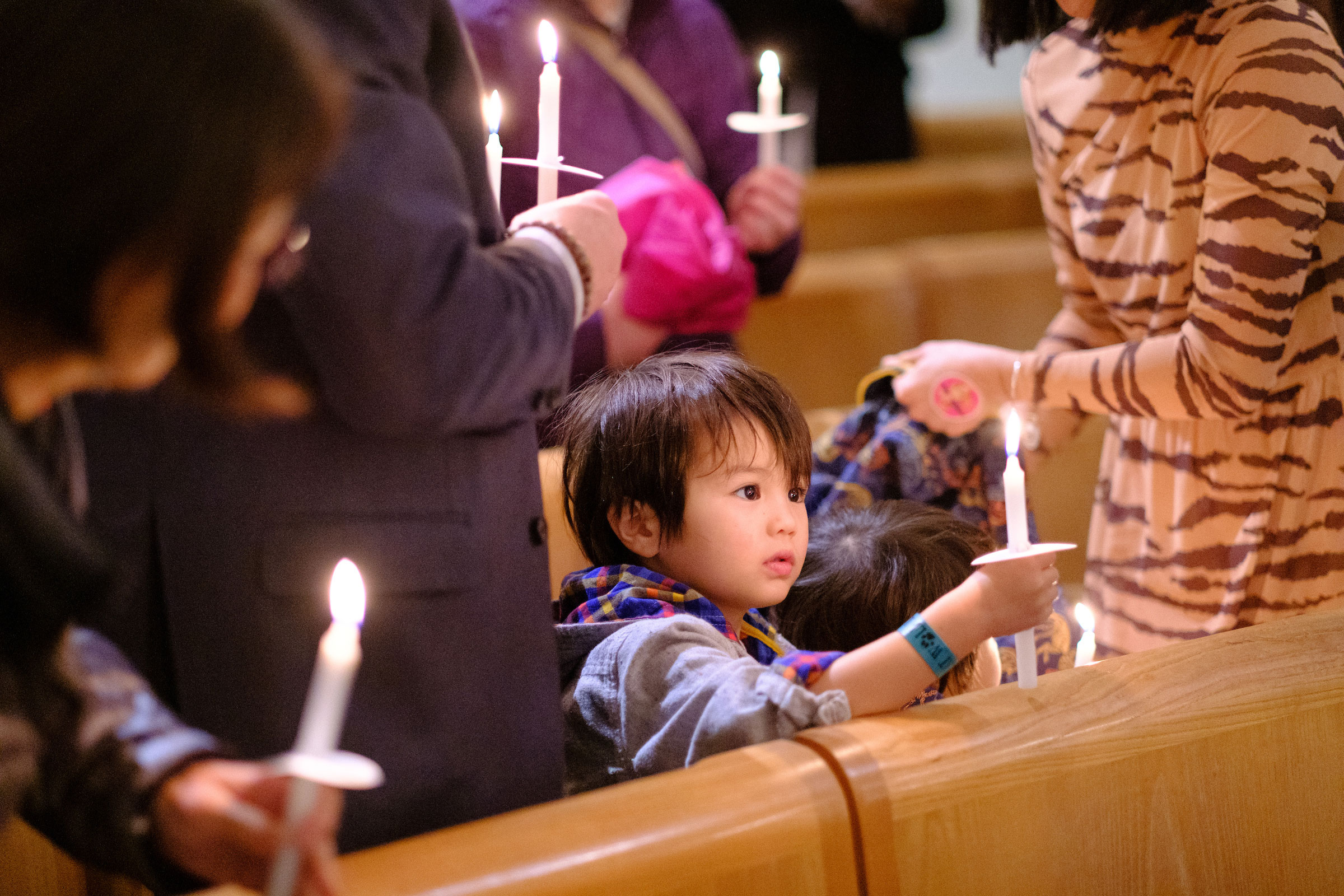 a young child holds a candle at the Advent Mass