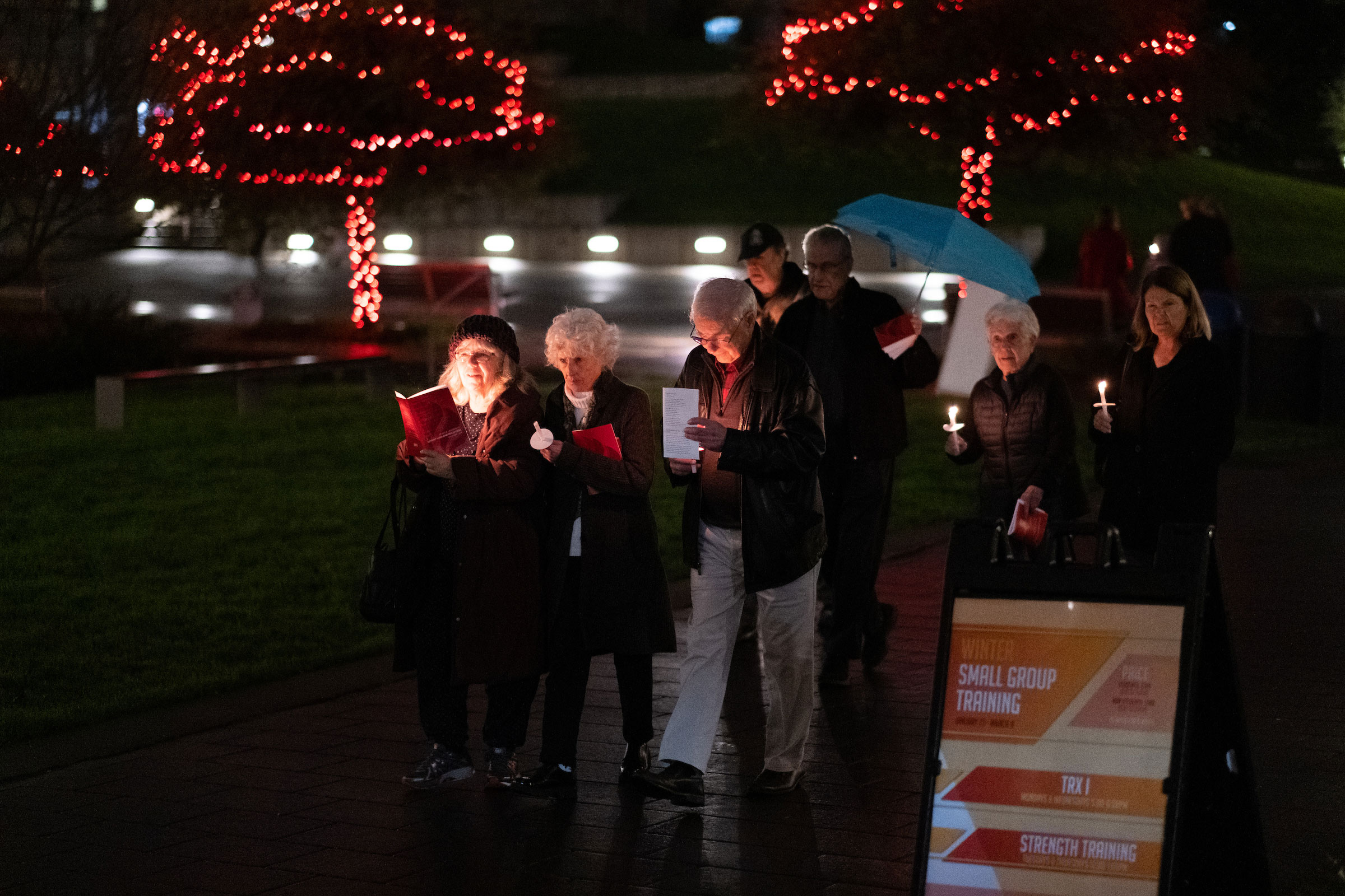 Advent Mass attendees walk with lit candles on campus