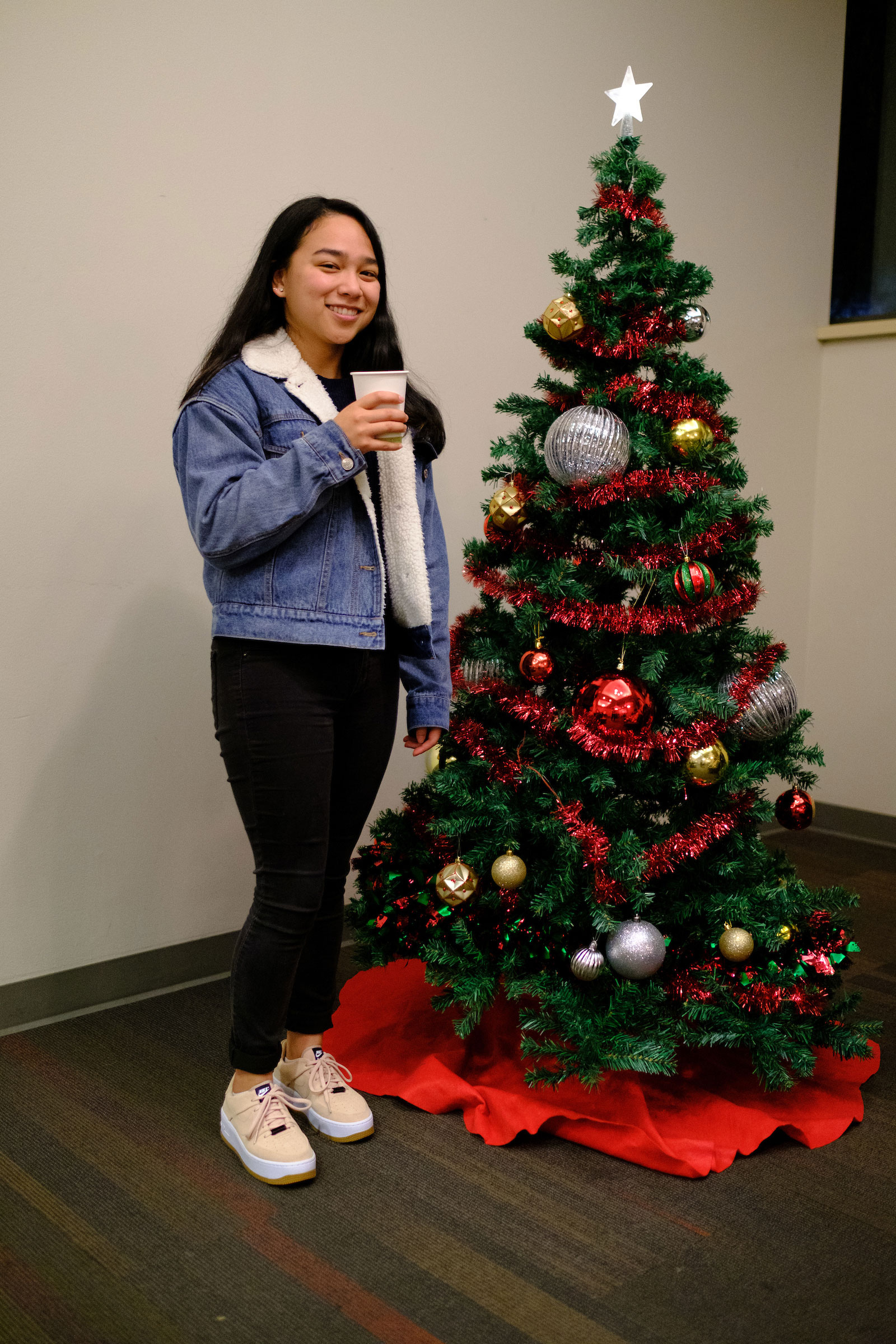 a student poses for a camera shot with a decorated Christmas Tree in the student center